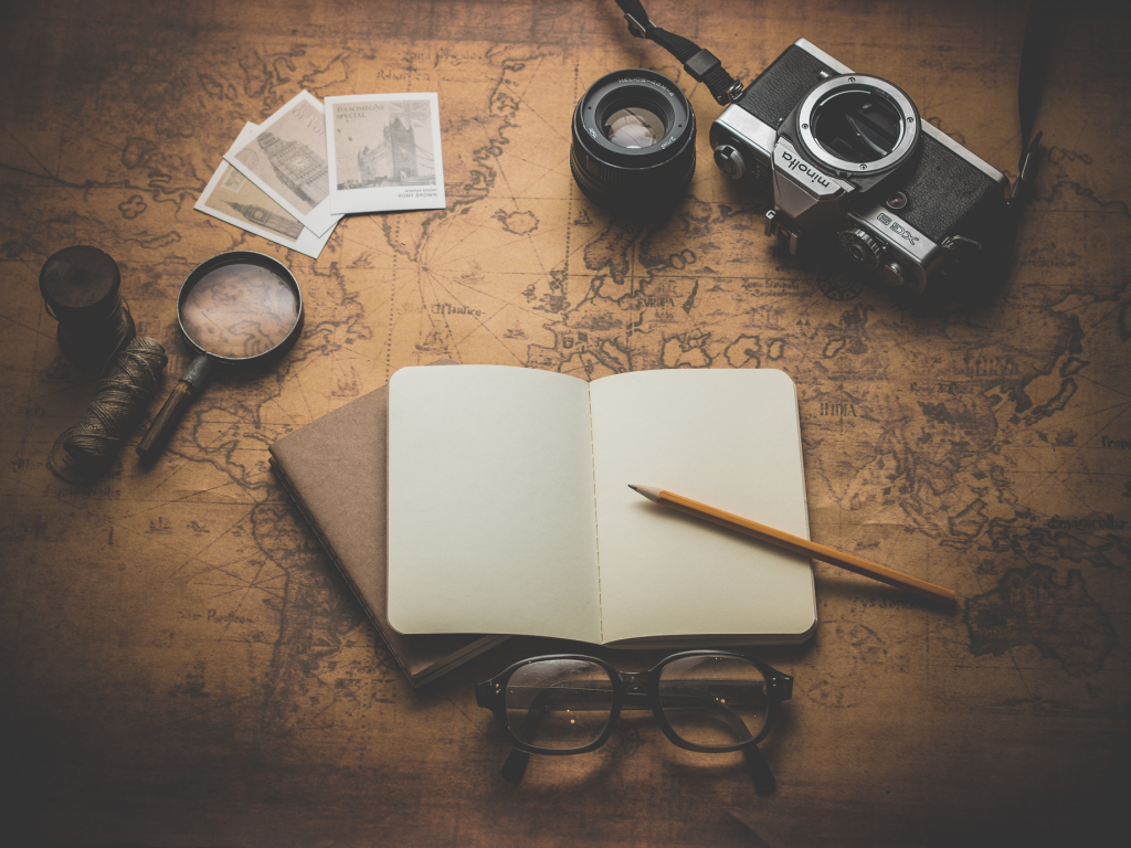 Weltkarte mit einer Kamera, Lupe und eine Buch.