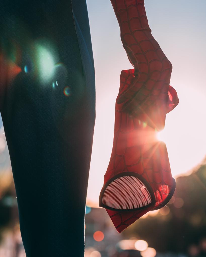 Mann in Spider-Man Kostüm mit abgezogener Maske